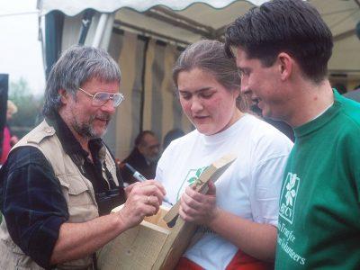 Bill Oddie signing an autograph on a bird box. Thatcham 1995